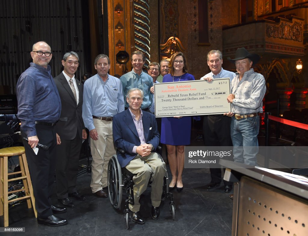 The San Antonio Auto Dealers Association presents a $20,000 check to the Rebuild Texas Relief Fund to Founder/CEO of Messina Touring Group Louis Messina, San Antonio Mayor Ron Nirenberg, Governor of Texas Greg Abbott, the Cavender Auto Family- Stuart Cavender, Cavender Chevrolet, Bobby Cavender, Cavender Buick GMC, Billy Cavender, Cavender Cadillac, Stephen Cavender, Cavender Toyota, Pamela Johnston Crail, President, San Antonio Auto Dealers Assocication; Rick Cavender, Cavender Audi and Chairman of SA Auto Dealers Association and Country Icon George Strait during a Press Conference held prior to Hand In Hand Texas Benefit Concert at Majestic Theatre on September 12, 2017 in San Antonio, Texas.