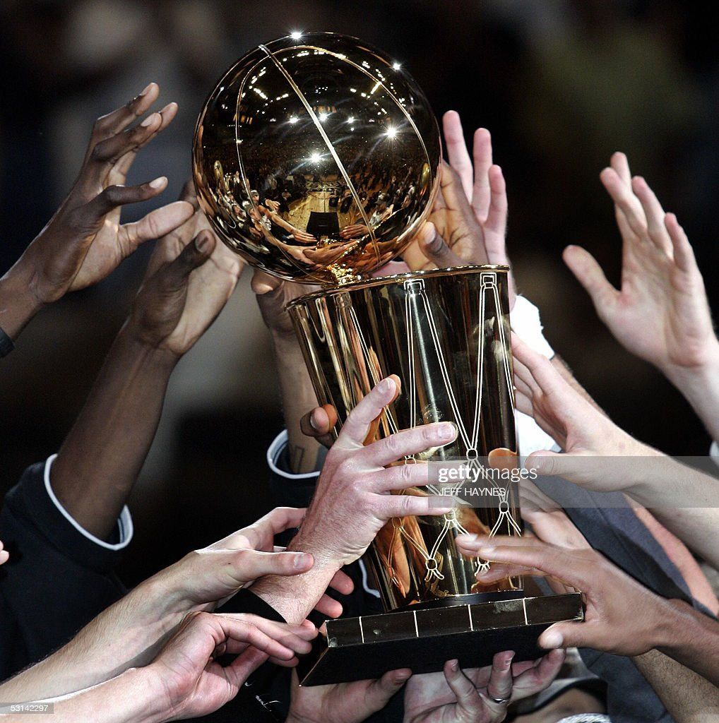 The San Antonio Spurs grab for The Larry O'Brien NBA Championship Trophy after beating the Detroit Pistons in the NBA Finals game seven 23 June, 2005 at the SBC Center in San Antonio, Texas. The Spurs won the game 81-74 to win the seven game series 4-3. AFP PHOTO/JEFF HAYNES