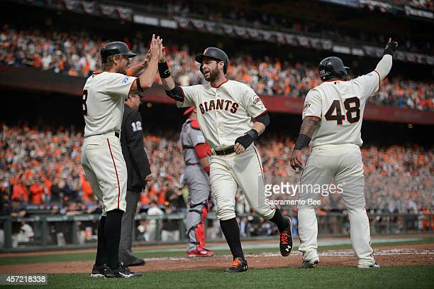 The San Francisco Giants' Hunter Pence Brandon Belt and Pablo Sandoval score on a double by Travis Ishikawain the first inning against the St Louis...