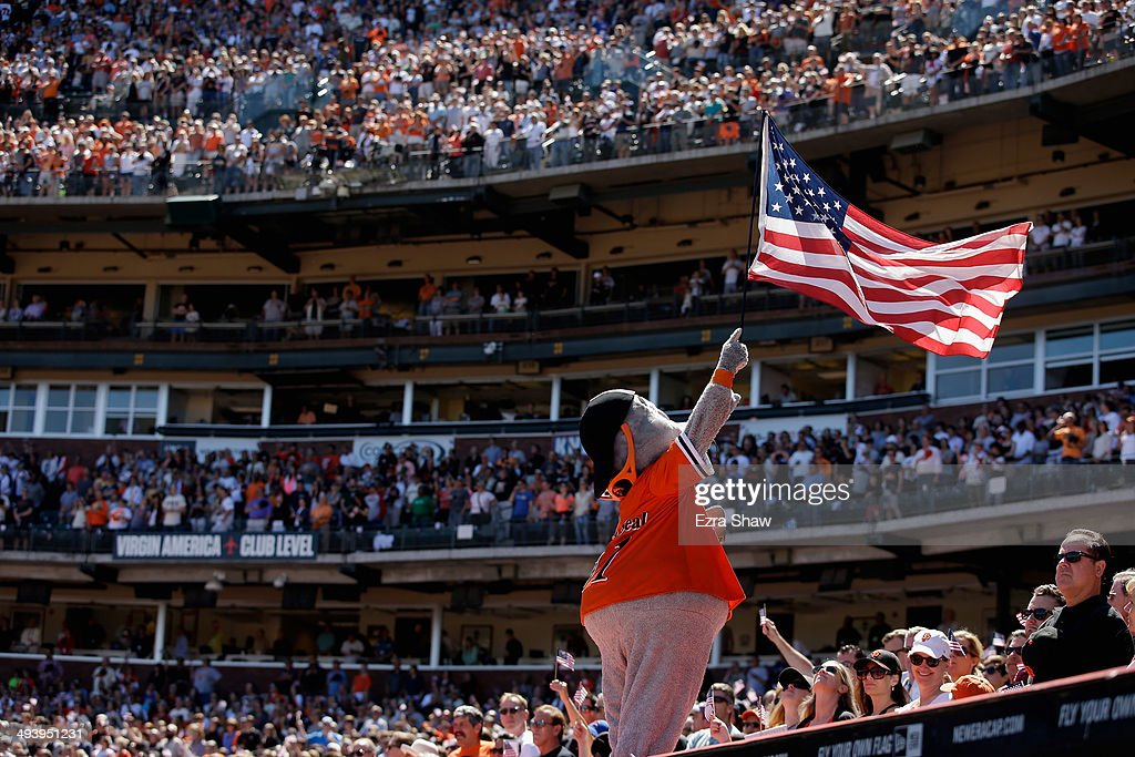 The San Francisco Giants mascot Lou Seal holds up an American Flag during the playing of God Bless America during their game against the Chicago Cubs at AT&T Park on May 26, 2014 in San Francisco, California.