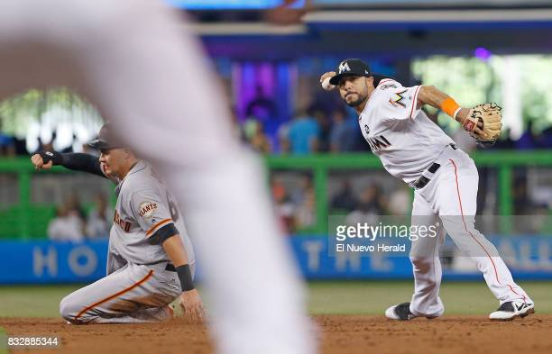 The San Francisco Giants' Ryder Jones left slides into second base as Miami Marlins shortstop Mike Aviles is unable to complete a double play during...