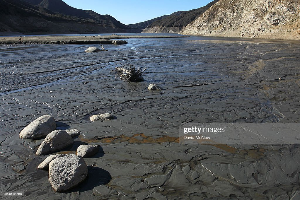The San Gabriel River passes over mud in the dry upper reaches of San Gabriel Reservoir in the Angeles National Forest on January 22, 2014 in near Azusa, California. Now in its third straight year of drought conditions, California is experiencing its driest year on record, dating back 119 years, and reservoirs throughout the state have low water levels. Unseasonable dangerous wildfire weather helped spread the nearby 1,952-acre Colby Fire which firefighters are about to contain but not before it destroyed five homes, damaged 17 others and injured six people. Gov. Jerry Brown officially declared a drought emergency on Friday to speed up assistance to local governments, streamline water transfers and potentially ease environmental protection requirements for dam releases.