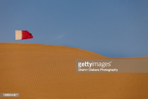 The sand dunes of Qatar with Qatar flag : Stock Photo