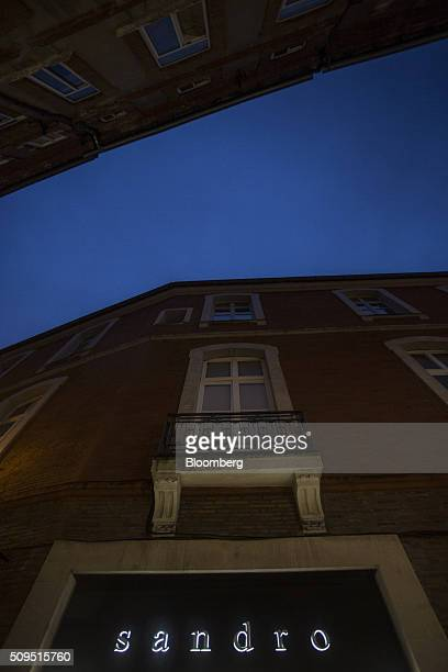 The Sandro logo sits illuminated outside a luxury clothing store operated by SMCP Group in Toulouse France on Wednesday Feb 10 2016 Shandong Ruyi...