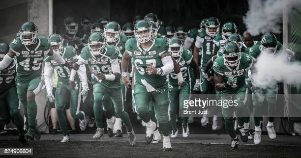 The Saskatchewan Roughriders lead by Dan Clark Duron Carter Bakari Grant Kacy Rodgers II take the field for the game between the Toronto Argonauts...