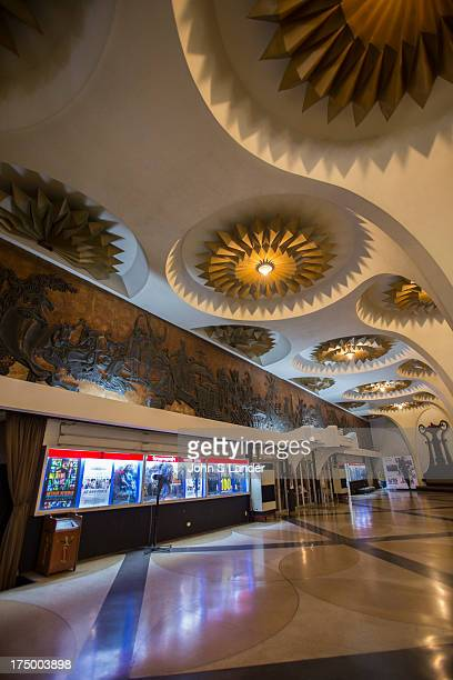 The Scala Cinema foyer is made up of a huge domed ceiling ornately decorated with art deco bronzed flowers The double circular staircases wind up to...
