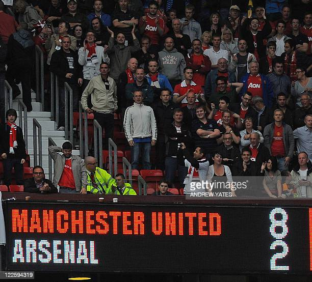 The scoreboard displays the 82 scoreline during the English Premier League football match between Manchester United and Arsenal at Old Trafford in...