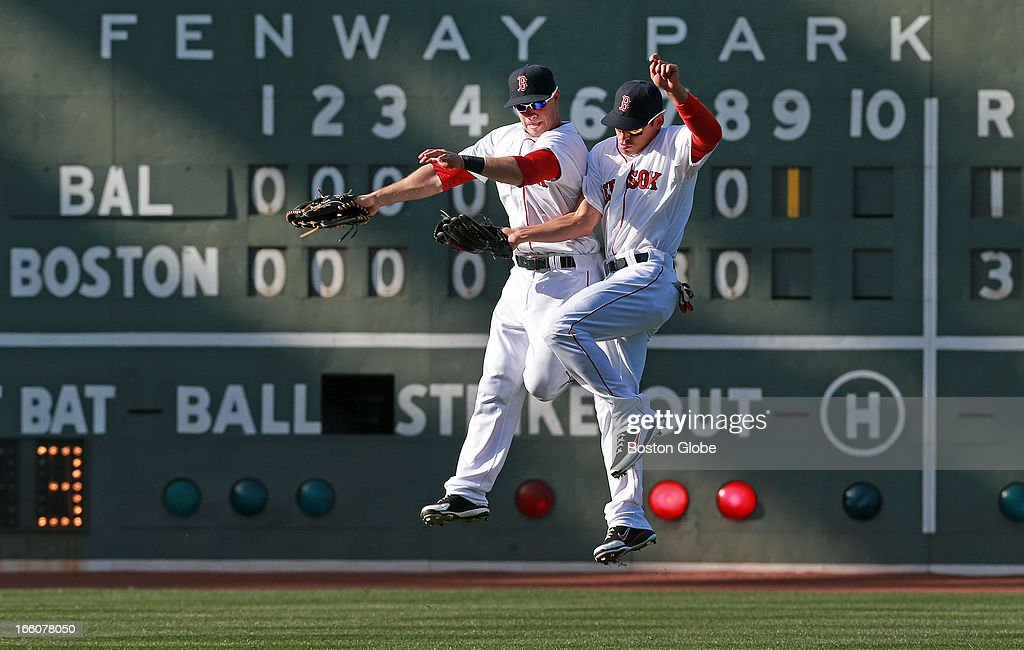 The scoreboard tells the story, as Red Sox outfielders Daniel Nava, left, and Jacoby Ellsbury, center, leap in celebration following the final out of the game. Nava's seventh inning three-run home run was the difference, as Boston downed Baltimore 3-1. The Baltimore Orioles play the Boston Red Sox during Opening Day at Fenway Park.