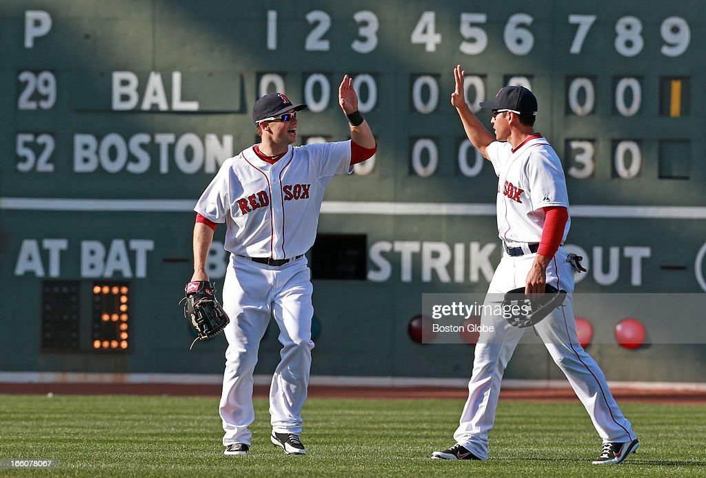 The scoreboard tells the story, as Red Sox outfielders Daniel Nava, left, and Jacoby Ellsbury, right, celebrate following the final out of the game. Nava's seventh inning three-run home run was the difference, as Boston downed Baltimore 3-1. The Baltimore Orioles play the Boston Red Sox during Opening Day at Fenway Park.