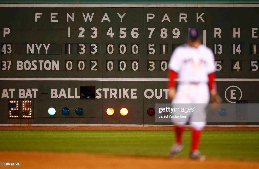 The scoreboard under the Green Monster shows a score of 13-4 in the 9th inning between the Boston Red Sox and the New York Yankees during the game at Fenway Park on April 24, 2014 in Boston, Massachusetts.