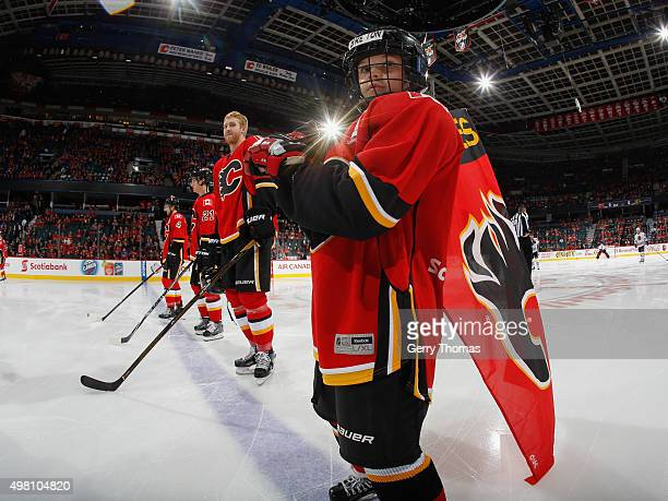 The Scotiabank skater stands with the Calgary Flames during the anthems prior to the game against the Chicago Blackhawks at Scotiabank Saddledome on...