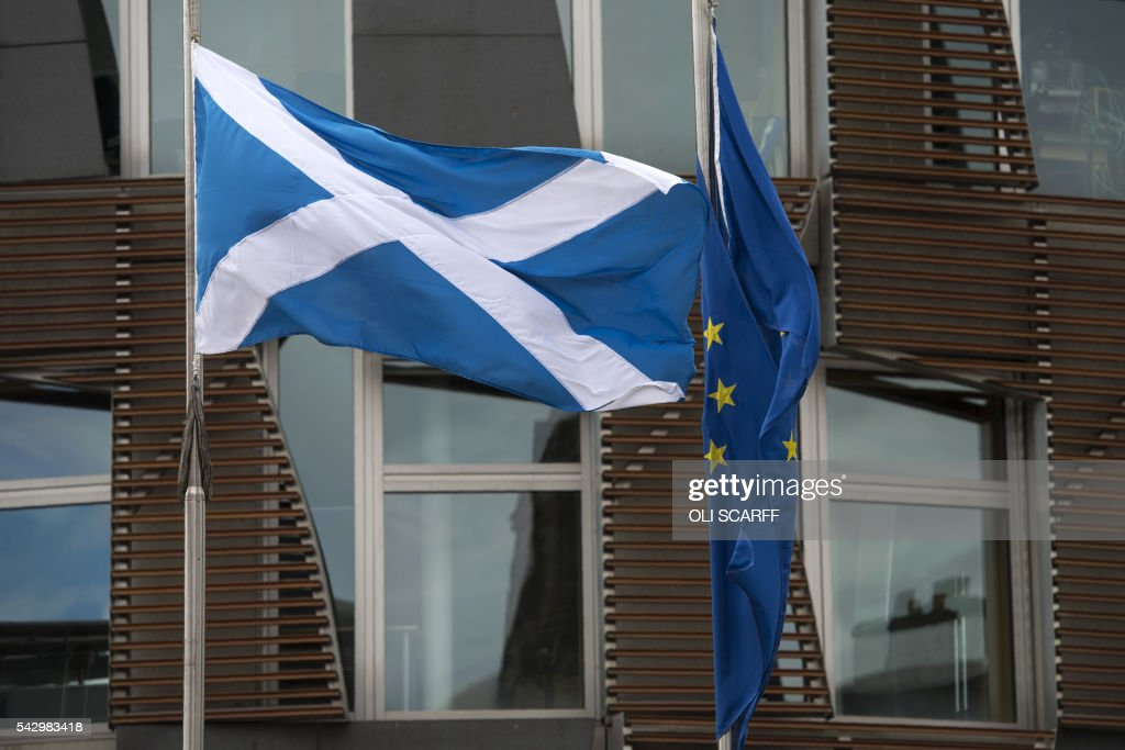 The Scottish Saltire flag (L) and the European Union (EU) flag fly outside the Scottish Parliament building in Edinburgh, Scotland on June 25, 2016, following the pro-Brexit result of the UK's EU referendum vote. The result of Britain's June 23 referendum vote to leave the European Union (EU) has pitted parents against children, cities against rural areas, north against south and university graduates against those with fewer qualifications. London, Scotland and Northern Ireland voted to remain in the EU but Wales and large swathes of England, particularly former industrial hubs in the north with many disaffected workers, backed a Brexit. / AFP / OLI