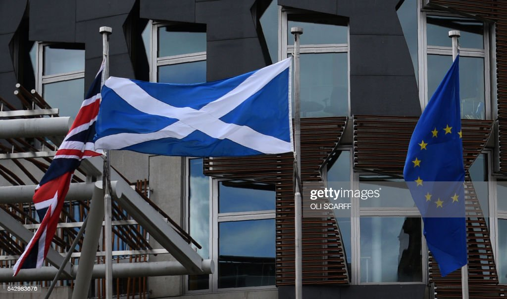 The Scottish Saltire flag (C) flies between the European Union (EU) flag (R) and the Union flag outside the Scottish Parliament building in Edinburgh, Scotland on June 25, 2016, following the pro-Brexit result of the UK's EU referendum vote. The result of Britain's June 23 referendum vote to leave the European Union (EU) has pitted parents against children, cities against rural areas, north against south and university graduates against those with fewer qualifications. London, Scotland and Northern Ireland voted to remain in the EU but Wales and large swathes of England, particularly former industrial hubs in the north with many disaffected workers, backed a Brexit. / AFP / OLI