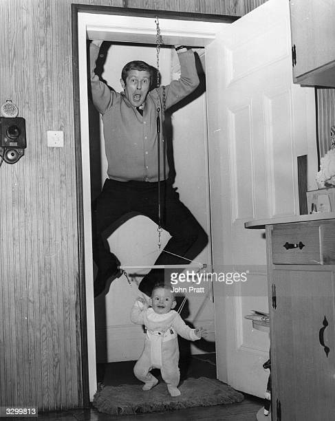 The Scottish star of the Black and White Ministrel Show Don Arrol at his home in Surrey hanging from the door frame while his baby daughter Fiona...