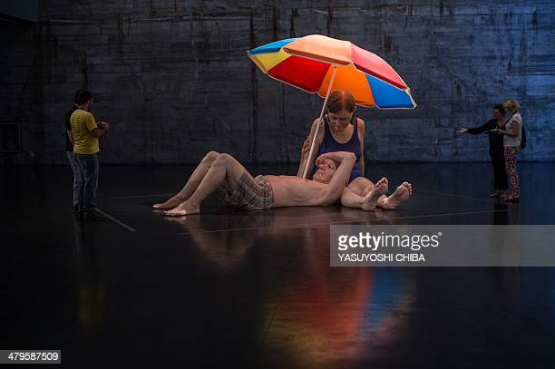 The sculpture titled 'Couple under an Umbrella' by Australian artist Ron Mueck is displayed at the Museum of Modern Art in Rio de Janeiro Brazil on...