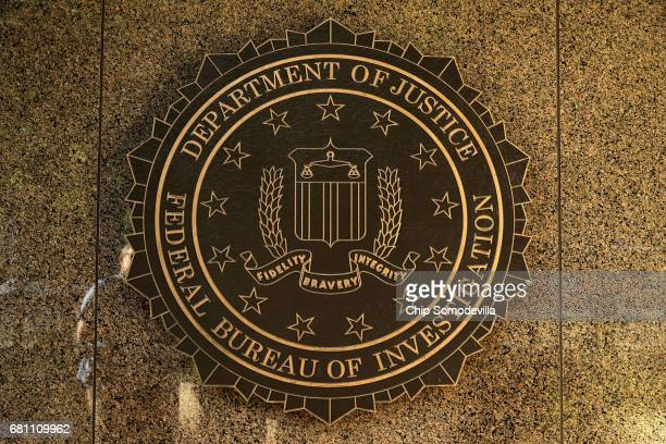 The seal of the Federal Bureau of Investigation hangs on the outside of the bureau's Edgar J Hoover Building May 9 2017 in Washington DC On the...