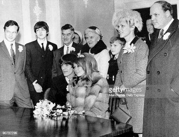 The seated newlyweds pose for the camera surrounded by family and friends including the Beatles's manager Brian Epstein Paul McCartney and the...