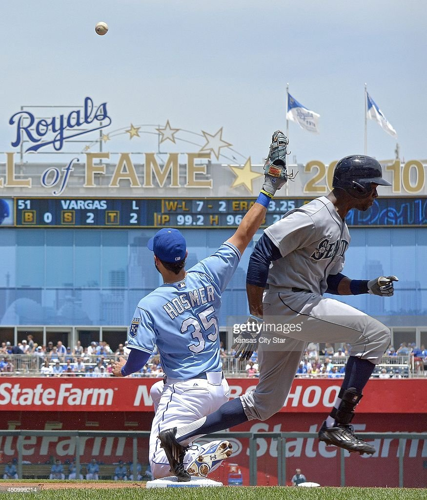 The Seattle Mariners' James Jones reaches first on a throwing error to Kansas City Royals first baseman Eric Hosmer by shortstop Alcides Escobar in...