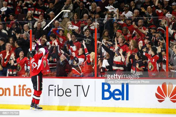 The second star of the game Derick Brassard of the Ottawa Senators tosses his stick over the glass for a fan following their overtime win against the...