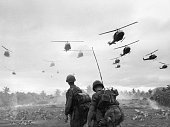 The second wave of combat helicopters of the 1st Air Cavalry Division fly over an RTO and his commander on an isolated landing zone during Operation...