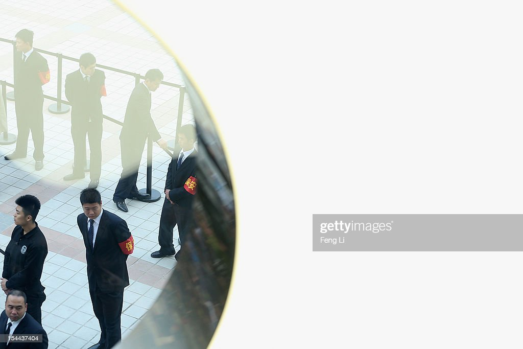 The security guards look on under the Apple's logo as Chinese consumers entering the newly opened Apple Store in Wangfujing shopping district on October 20, 2012 in Beijing, China. Apple Inc. opened its sixth retail store on the Chinese mainland Saturday. The new Wangfujing store is Apple's largest retail store in Asia.