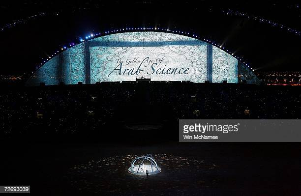 The 'Seeker' and his son perform below the LED screen during the Opening Ceremony of the 15th Asian Games Doha 2006 at the Khalifa stadium on...