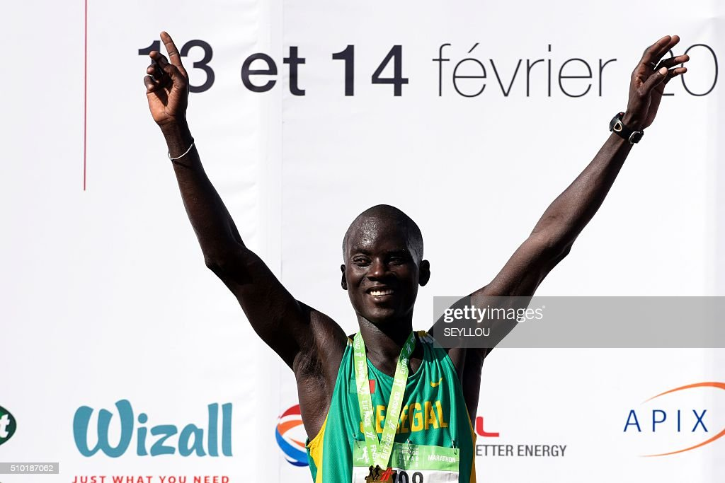 The Senegalese athletes Samba Faye celebrates after being the fisrt Senegalese to cross the finish line during the first ever Dakar International Marathon long 42,195km in Dakar on February 14, 2016. The competition organised by the BTP Eiffage society started on February 13 in front of International Conference Center Abou Diouf (Cicad) on the outskirts of Dakar with different runs of 10 km and will end the day after, February 14, with a marathon. The BTP Eiffage society hosted the event to celebrates its 90 years of presence in Senegal. / AFP / SEYLLOU