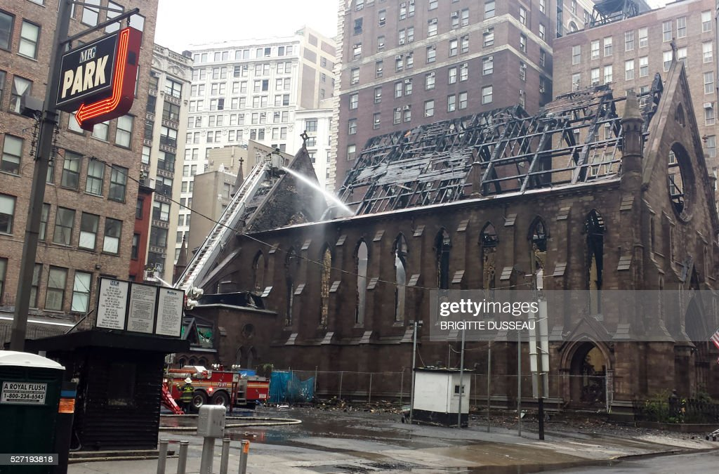 The Serbian Orthodox Cathedral of Saint Sava is viewed on May 2,2016 after a massive fire destroyed the church in Manhattan, New York on May 1, 2016. More than 700 parishioners had celebrated Easter earlier in the day and enjoyed a luncheon, but the cathedral was empty when the fire started. Firefighters are still dousing the building with water this morning. / AFP / Brigitte DUSSEAU