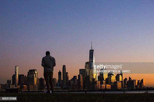 TOPSHOT The setting sun casts light on lower Manhattan and One World Trade Center in New York City on December 20 2016 as seen from Hoboken New...