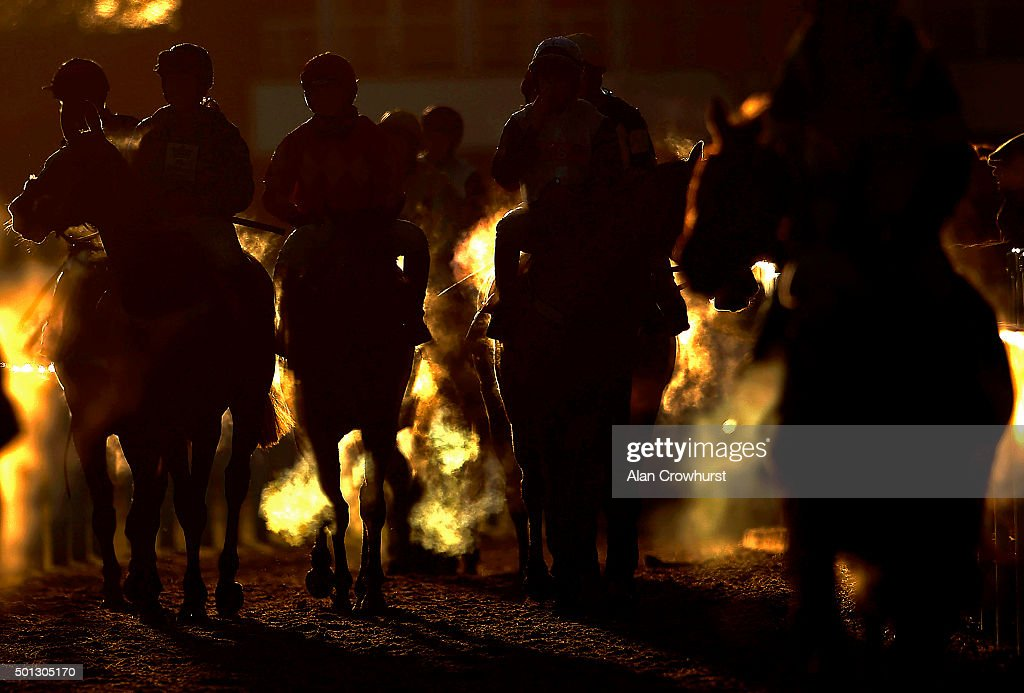 The setting sun lights the steam rising from the runners as they return after finishing at Cheltenham racecourse on December 11 2015 in Cheltenham...
