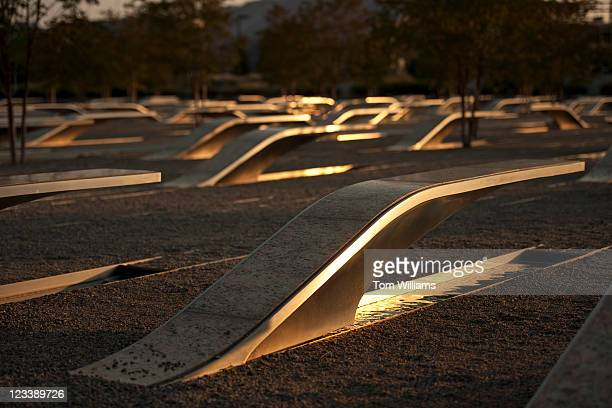 The setting sun reflects off benches at the Pentagon Memorial outside of the Pentagon in Arlington Va Each bench is dedicated to one of the 184...