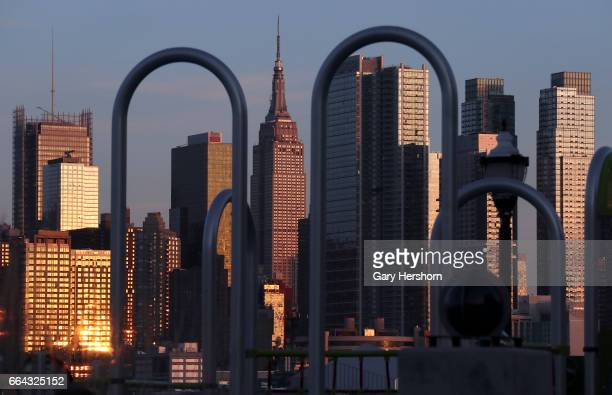 The setting sun reflects off buildingS on the skyline of New York City on April 2 as seen from Weehawken NJ