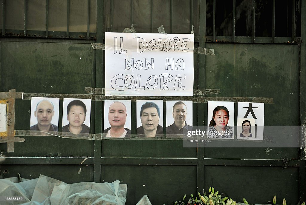 The seven photos of Chinese workers hang outside of a burned clothing factory where they died, with a sign reading 'Il dolore non ha colore' (The pain has no color) on December 4, 2013 in Prato, Italy. Seven people died and three were injured December 1, when a Chinese clothing factory in the industrial district of the Italian town of Prato in Tuscany burned, killing the workers trapped in a factory dormitory, where workers sleep, eat, and work.