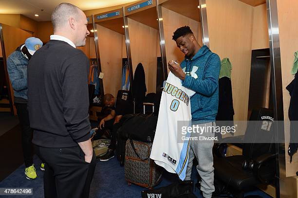The seventh selection in the 2015 NBA Draft Emmanuel Mudiay of the Denver Nuggets meets Head Coach Mike Malone after arriving for a press conference...