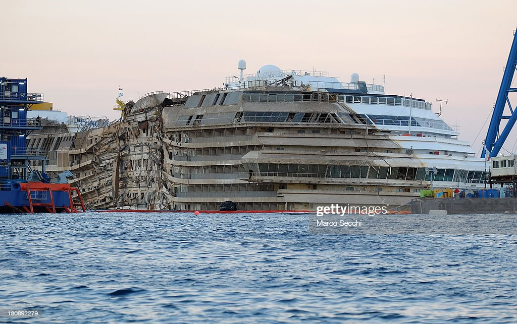 The severely damaged side of the stricken Costa Concordia is visible after the parbuckling salvage operation successfully uprighted the ship at around 4 am on September 17, 2013 in Isola del Giglio, Italy. Work began yesterday to right the stricken Costa Concordia vessel, which sank on January 12, 2012. If the operation is successful, it will then be towed away and scrapped. The procedure, known as parbuckling, has never been carried out on a vessel as large as Costa Concordia before.
