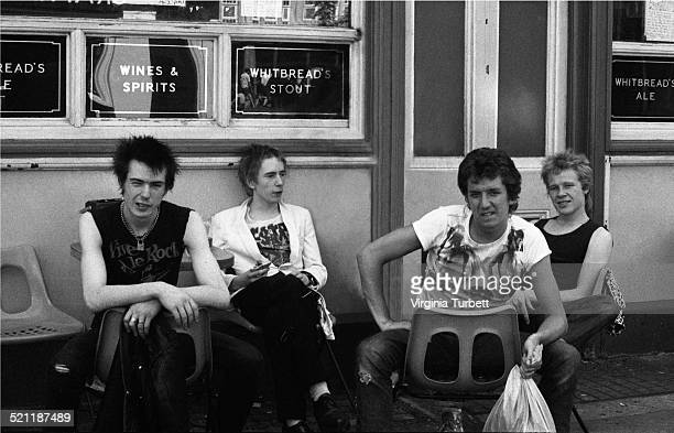 The Sex Pistols sit outside a pub during a break from recording a video for the song 'Pretty Vacant' London June 1977 LR Sid Vicious Johnny Rotten...