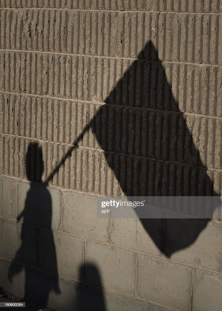 The shadow of a Bahraini Shiite Muslim holding his national flag is seen on a wall during an anti-government rally to demand reforms in the village of Malikiya, South of Manama, on February 3, 2013. The Gulf state has been shaken by unrest since its forces in March 2011 crushed a month of popular Shiite-led protests demanding greater rights and an end to what they said was discrimination by the Sunni royals. AFP PHOTO/MOHAMMED AL-SHAIKH