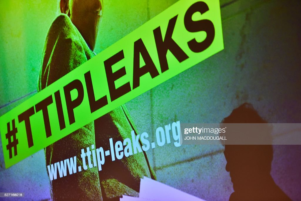 The shadow of a Greenpeace member is cast on a projection during a press conference where Greenpeace presented classified papers from ongoing US-EU trade talks on May 2, 2016 at the re:publica conference on internet and society in Berlin. Greenpeace published documents showing that the Transatlantic Trade and Investment Partnership (TTIP) poses 'major risks for climate, environment and consumer safety'. / AFP / John MACDOUGALL