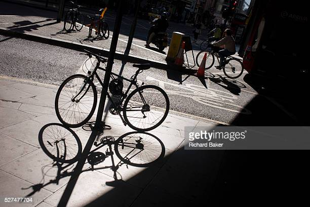 The shadow of a locked up bike is on a central London street as a cyclist passesby The sun is sinking behind tall office buildings and is...