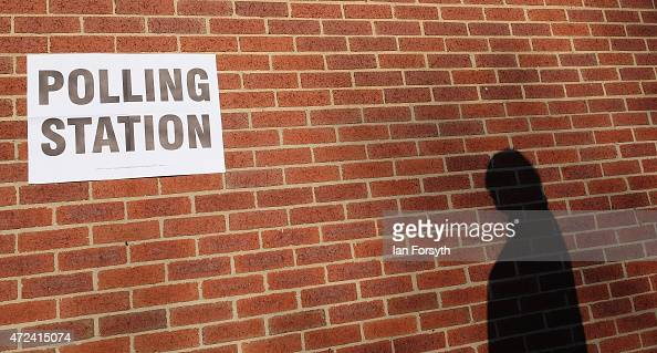 The shadow of a man going to vote is cast on a wall outside a polling centre in a bowling club on May 7 2015 in Redcar England The nation goes to the...