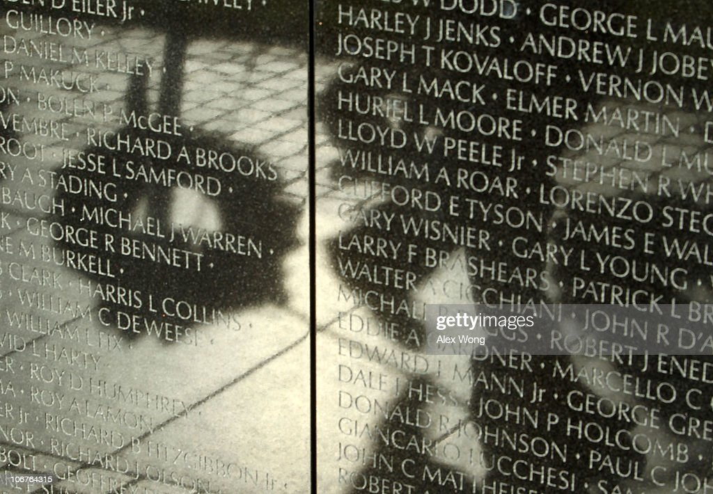 The shadow of a man passing by a wreath is reflected on the walls of the Vietnam Veterans Memorial after a Veterans Day event November 11, 2010 in Washington, DC. The nation's veterans were honored and remembered during the annual Veterans Day.