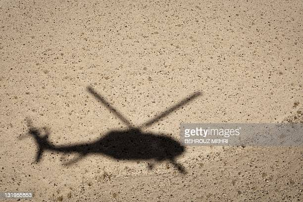 The shadow of a medevac helicopter from the US Army's Task Force 'Dust Off' Charlie Company 1171 Aviation regiment is seen as they fly over the...