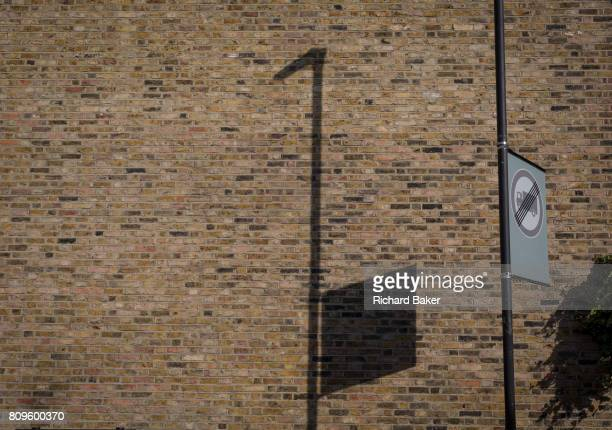 The shadow of a nearby lamp post and square traffic sign on the brick wall of an end terraced home on 3rd July 2017 in Herne Hill London England