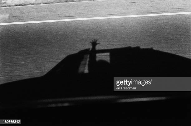 The shadow of a person waving from a car in motion 1970