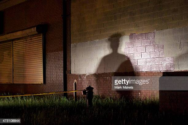 The shadow of a police officer is cast onto a building near the wreckage of an Amtrak passenger train that derailed carrying more than 200 passengers...
