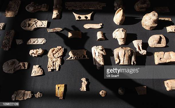 The shadow of a technician at the British Museum is posed to hold a piece of carved ivory from ancient Assyria recently acquired by the British...