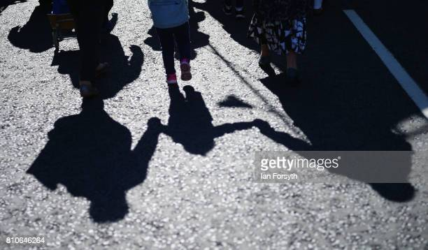 The shadow of a young girl is cast on the road as she marches with her parents through Durham city during the 133rd Durham Miners Gala on July 8 2017...