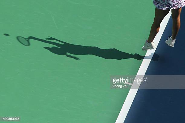 The shadow of Alexandra Dulgheru of Romania serves during the match against Ana Ivanovic of Serbia on Day 2 of 2015 Dongfeng Motor Wuhan Open at...
