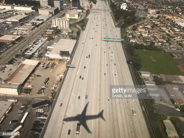 The shadow of an airline is displayed on Highway 405 seconds before landing in Los Angeles international airport on February 22 2017 / AFP PHOTO /...