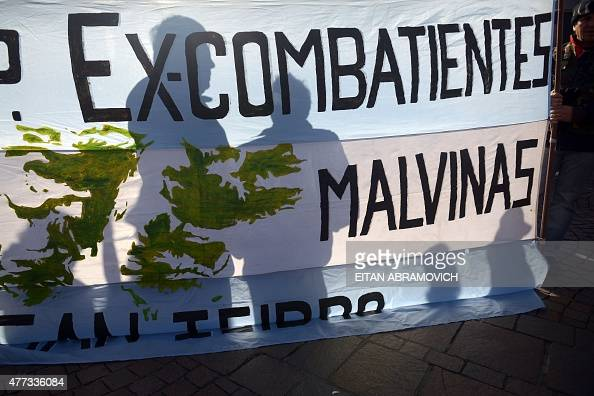 The shadow of Argentinian veterans of the 1982 Falklands War between Great Britain and Argentina is casted on a banner as they march towards the...